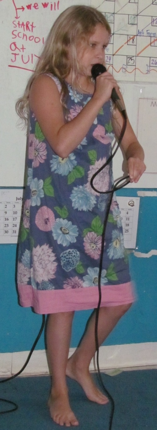 Young girl standing in front of a classroom holding a microphone singing.